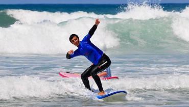 Aufstehen und die Balance halten sind die ersten Schritte für Anfänger im Surfurlaub.