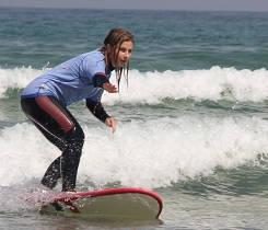 Technikschulung durch qualifizierte Surflehrer. Eine Teilnehmerrin lernt Turns in ihrem Surfurlaub.